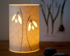 This little tea light cover is like mini flickering version of one of my lamps. It has a really gorgeous glow. It is 13 cm (5.1) high and 9 cm (3.3) in diameter. It comes with a glass votive to put your tea light candle in and it must only be used with the glass for safety! For indoor use only. The design is cut laser cut from paper and laminated for strength and durability and to create the bright white layer when lit. The lamp is constructed in my studio in Hebden Bridge…