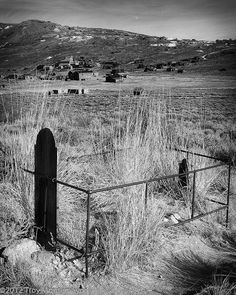 Tombstone, Bodie, CA    A wooden tombstone and pipe fence mark an overgrown grave in the cemetery overlooking the ghost town in Bodie, California.
