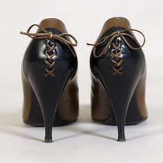 Brown and black leather pumps, ca. 1960, with lacing detail. www.vintageclothin.com