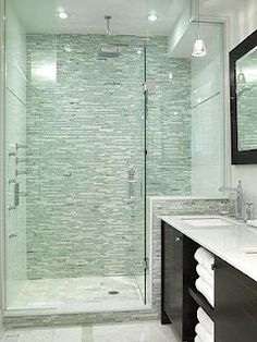 The colour palette and materials arent right but the shape and size of this shower is similar to yours except with glass.  If you imagine this as a solid wall to the right, this layout could work and give you a slightly bigger vanity. Or you could stick with a glass panel to give you an open look