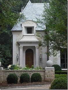 A home with an exterior of stone, accented by a limestone door surround that has a very French style.
