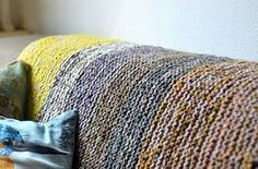 This super simple garter stitch blanket has an I-cord edge and is worked with two strands of worsted weight yarn held double. I used several skeins of yarn from my stash that resulted in a colorful squishy blanket. It's a great project for mindless knitting and with US 15 / 10mm needles, it eats delicious yarn in no time at all, leaving lots of empty space in your yarn box or cabinet or room to fill with new wooly acquisitions.