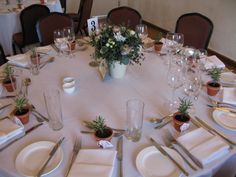 Tables in The Watermill with flower filled enamel buckets and mini pots of rosemary.