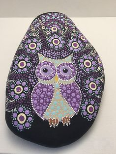 Purple mandala rock with owl focal point. Colors used are shades of purple, blue, cream, and light brown. Use of acrylic paint on a river rock. Finished with spray on glaze for a shiny finish.