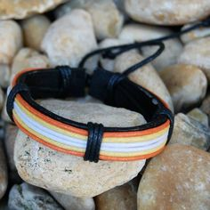 CLEARANCE Black/Orange/Yellow/White Leather B Black leather bracelet with orange, yellow and white cords on a pull string. One size fits most. KSAR Jewels Jewelry Bracelets