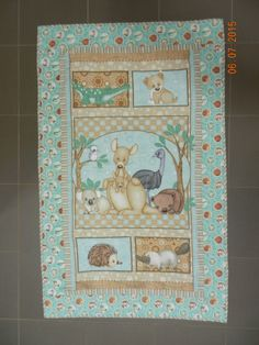 Cot Quilt, Australian baby animals panel. Mostly free motion quilting.Heavy additional    quilting on both the Emu & the Echidna. Other quilting done to mimic Native Australian art.