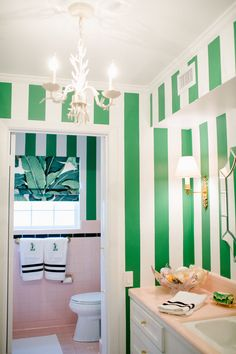 Green & white stripes + banana leaf fabric partners with vintage pink tile to create this Palm Beach Chic meets Beverly Hills Hotel inspired bathroom!