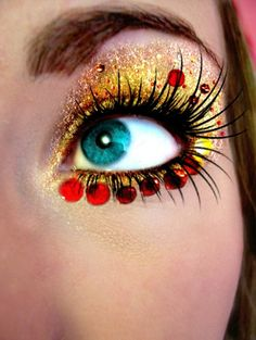 .gold eyes red bling. Eye make up. Face jewels . Party night. Costume makeup Beautiful eye bling