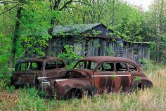 Abandoned, rusty old Ford and Chevy cars next to a delapidated barn; Old Abandoned Buildings, Abandoned Places, Abandoned Vehicles, Haunted Places, Rust In Peace, Car Insurance Rates, Rusty Cars, Old Fords, Disney Cars