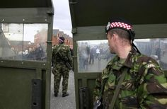Soldiers of 1st Argyll and Sutherland Highlanders man a barricade of Saxon armoured vehicles at the bottom of the Ardoyne Road during the sectarian stand-off at Holy Cross Primary School, Belfast on 10 September 2001. The Royal Ulster Constabulary and British Army were required to shield 45 Catholic children and their parents against approximately 200 Loyalists as they walked to school