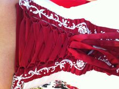 A wedding dress with red corset lined with hand embroidery and glass beads