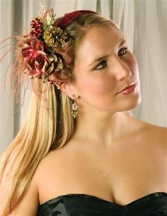 "HOLIDAY FASCINATOR - Those lavish headbands from decades past are experiencing a deserved renaissance. Covered in sumptuous burgundy velvet, this comfy headpiece is festooned with vintage-quality milliner's blooms and holiday trimmings. 7"". USA."