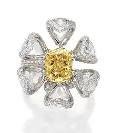 18 KARAT TWO-COLOR GOLD, COLORED DIAMOND AND DIAMOND 'DAY & NIGHT' RING, NIRAV MODI. The flowerbud centered by a cushion-cut Fancy Vivid Yellow diamond weighing 3.01 carats, enahnced by numerous round diamonds of yellow hue, framed by six articulated petals set with 18 calibré-cut diamonds which are adjustable as to be worn as an elegant flower blossom, set throughout with numerous round near colorless diamonds, the near colorless diamonds weighing 9.25 carats, size 6, with maker's marks.