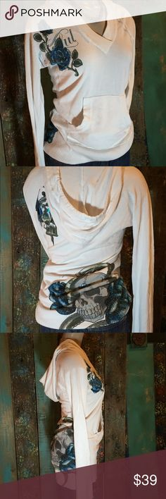 Sinful white long sleeve pullover hoodie size Med This shirt is super cute! It has the hood on back, blue and black designs with sequins. Thick elastic bottom to wear straight down or bunch up. It is in excellent condition and is a size Medium Sinful Tops Sweatshirts & Hoodies