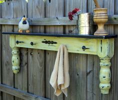 Unique combination of display shelf, coat or towel rack and funky wall art all in one! This piece has been created from a retired coffee table and given a highly distressed finished with layers of antique white, black and mustard yellow paint.