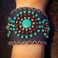 """Boho Handmade Leather Cuff w/Turquoise Beads Beautiful Handmade Boho Leather Cuff Bracelet with real Turquoise, amber crystal and gold beads. Made by Fair Trade, this stunning cuff is so awesome, I am sad to sell it. I just never wear it, and it deserves to be seen. Dark, brownish-grey leather, with 2 snap closures for a tighter or looser fit. Measures approximately 8.25"""" x 2.5"""". Perfect condition. Handmade Jewelry Bracelets"""