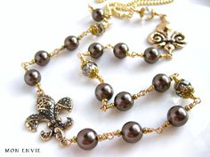 Wire Wrapped Beaded Fleurdelis Long Necklace, Swarovski Dark Brown Pearls, Chinese Crystal Faceted Glass Beads, Gold Chain. $25.00, via Etsy.