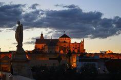 Cordoba al anochecer, de noche, la mezquita y el angel sobre el puente bajo el Guadalquivir
