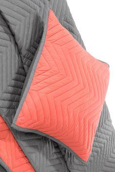 Charleston Kissen und Tagesdecke in Grau und Korallenrot. Die einfachste Art, deinem Schlafzimmer einen frischen Style zu verpassen? Die richtige Decke und passende Kissen! Charleston hat den Look und nicht zuletzt unwiderstehlichen Kuschelfaktor.