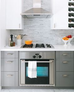 The IKEA cabinetry, spray-painted grey and white, takes its lead from the classic Carrara marble flooring.