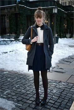 Black Tights. Navy Pleated Skirt. White Button Down W/ Black Collar. Charcoal Grey Jacket. Brown Belt. Mustard Yellow Bag.