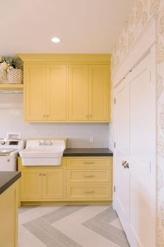 Yellow and gray laundry room features yellow shaker cabinets paired with charcoal gray quartz countertops and a white hex tiled backsplash accented with gray grout.