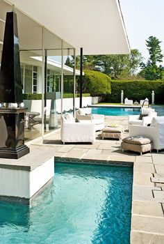 A comfortable outdoor seating area sits between the swimming pool and small reflection pool.
