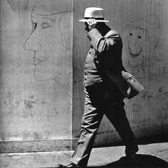 John Gutmann | Man Walking by Clown and Lady Graffiti, San Francisco 1939