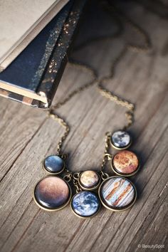 Solar system necklace -- you can make the planet pieces by taking a cutout of the planet, placing it over the base of your choice and using glass pebbles like mancala pieces over it.