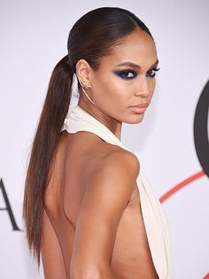 """GO SLEEK AND LOW Take the ponytail you wear while binge-watching Netflix, make it superstraight, and add a clean middle part and you have a style elegant enough for the red carpet. Case in point: Joan Smalls's incredibly chic ponytail for the CFDA Awards this year. Placement is key—secure your hair in the middle of the back of your head. """"It's much cooler than a low, low ponytail,"""" says hairstylist Jennifer Yepez. To make it sleek, Yepez ran over the tail with a flatiron, followed by a…"""