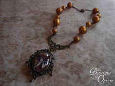Collier couleur bronze, orné de magnifiques perles dorée et d'un imposant médaillon. Le portrait du médaillon est celui de La Muse de Klimt, une femme rousse inspirée des peintures de Klimt.