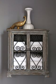 Wrought iron scroll inset into cabinet doors. Would look nice on a larger scale, too, as the picture is of a hanging shelf cabinet.