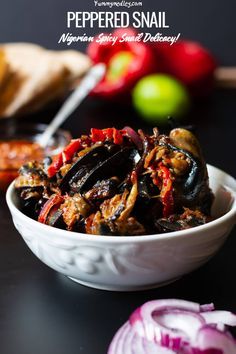 The spicy, chewy goodness of peppered snail consists of boiled snails sautéed in onions, peppers and spice. This spicy Nigerian snail dish is quite easy to prepare and is a guilty pleasure of a lot of Nigerian homes. Spicy Recipes, Seafood Recipes, Snails Recipe, West African Food, Gourmet Desserts, Plated Desserts, Nigerian Food, Molecular Gastronomy, International Recipes