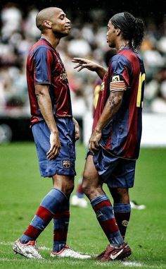 Thierry Henry and Ronaldinho playing for Barcelona discussing strategy.