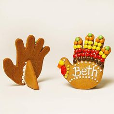 Cookie Turkey Place Card - classic gingerbread cookie recipe makes these turkey forms with the help of a hand-shape cookie cutter. Once the cookies are baked and cooled, use small candies and frosting to decorate the fingers to look like colorful feathers and the thumbs to resemble turkey faces. Use white icing to pipe guests' names onto the turkeys.
