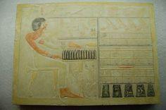 Ioenoe Afgietsel. De stèle toont een zittende man op een stoel zonder leuning, naar rechts gekeerd, gehuld in een lang gewaad met een strik op de linkerschouder. Hij draagt eEn korte pruik, zijn rechterarm is uitgestrekt naar de offertafel voor hem, de linkervuist ligt op de borst. Boven en onder de offertafel staan hiërogliefen en offergaven, geheel boven een tekstregel, rechts is een'kledingmagazijn'. Bron: Rijksmuseum van Oudheden, Leiden
