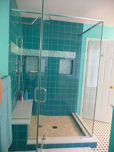blue tile shower, seat in shower, black and while tiled floors