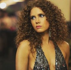 Amy Adams curly red hair and plunging to in American Hustle