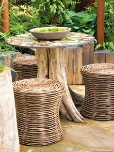 Basketweave containers as stools are a cost-effective way of bringing a rustic look to your outdoor space. You can create the look of this table by placing a tabletop or piece of glass atop sturdy logs or stumps.