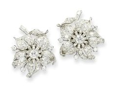 A PAIR OF DIAMOND EAR CLIPS   Each designed as an openwork single and circular-cut diamond flowerhead with diamond pistil, to the baguette and circular-cut diamond leaf and stem, mounted in platinum, late 1930s, 3.1 cm long