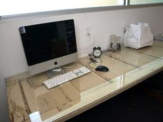 Floating Desk - Old door with a piece of glass on top and mounted to the wall with brackets.