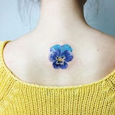Cool blue flower tattoo on spine