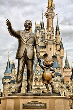 """Disney's Cinderella Castle - the iconic statue of Walt Disney known as """"Partners"""" Statue as it shows Mickey Mouse hand in hand with Walt Disney"""