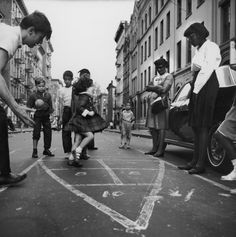 A view of children playing hopscotch in the street in Spanish Harlem