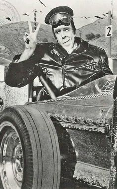 Herman Munster sitting in Grandpa Munster's Dragula Coffin Roadster