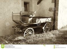 Photo about A monochromatic sepia image of an old world horse carriage with wooden wheels sitting outside a historic building in Switzerland. Image of finish, story, four - 105468745