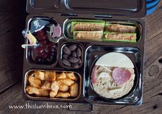 "So today I made a ""pirate lunch"" including a pirate sandwich with a heart shaped eye patch, celery and peanut butter (use sunbutter if peanut allergies are a concern), grapes, taco flavored Ellsworth cheese curds, almonds packed in a Planet Lunch Box"