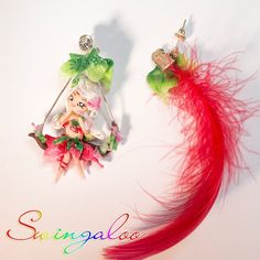 Pendant earrings, the pair consists in a Swingaloo fairy on a swing entirely covered with flowers and a red synthetic feather. These jewels are completely handmade by an Italian artist, the stud of the earrings is made of silver plated alloy.  Find it on www.Delicute.com