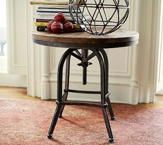 "Weldon Side Table #potterybarn Blonde wood pairs with natural iron for an appealing mix of textures on this table. Spin the top to adjust its height.  27"" diameter, 25–30"" high         Crafted of solid pine and iron. $599"