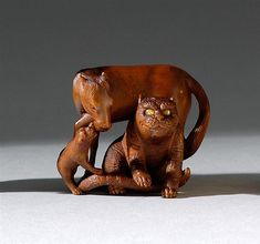 """WOOD NETSUKE Meiji Period By Yoshikazu. Depicting a tiger, horse, and puppy. Tiger and horse with inlaid eyes. Signed. Height 1.15"""" (3 cm). Ex Collection: Raymond Bushell."""